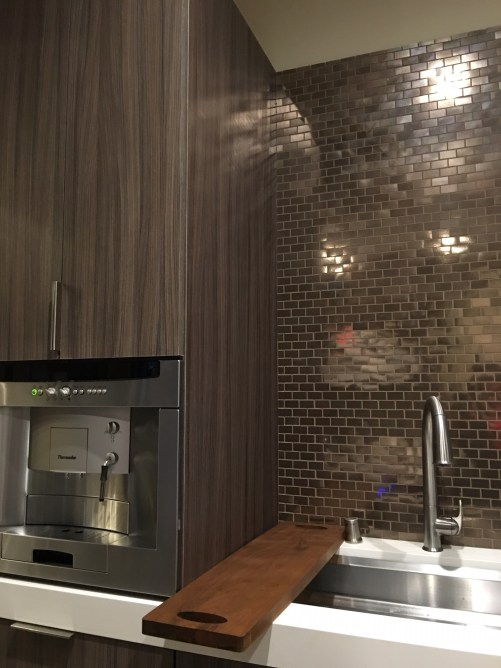 Thermador's built-in fully automatic coffee machine pairs well with Daltile's stainless steel mosaic tiles.