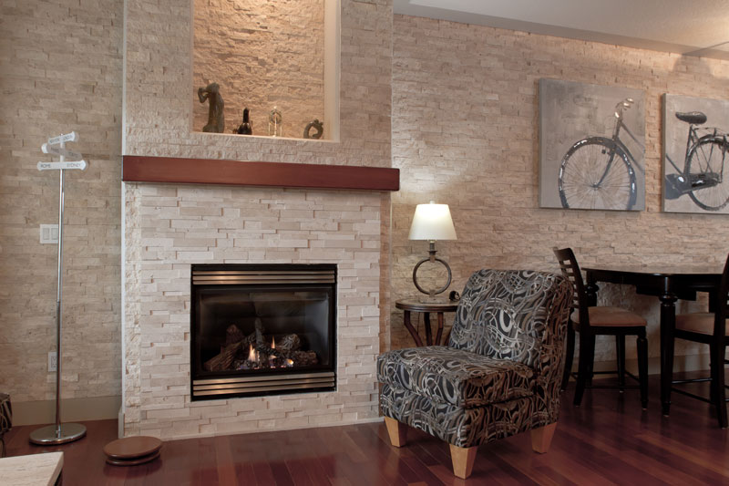 A fireplace and wall cladded with Ivory Splitface and Cubic Ledgestone