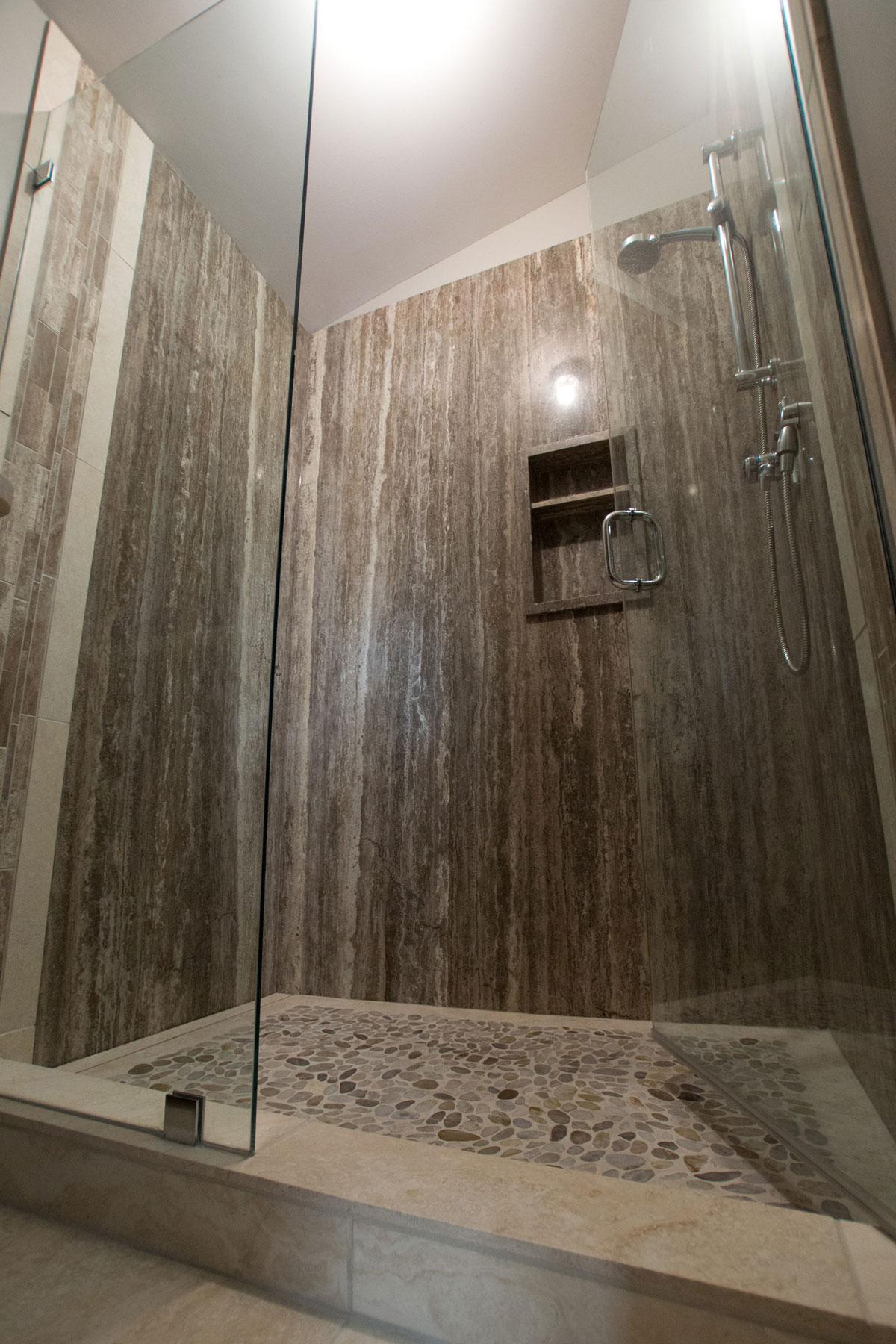 Persian Silver Bolder Panel, Cosme Travertine Random Strip, Baja White Travertine and Kootenay Pebbles Mosaic install in a shower