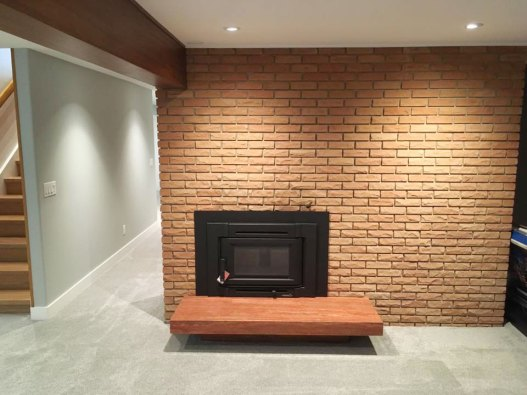 Red Travertine Bolder Stone Panel installed on a fireplace, surrounded by red brick