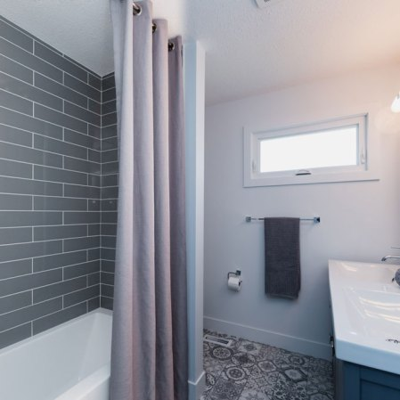 Marrakesh Grey Tile installed on the floor and Soho Taupe subway tile installed around the tub