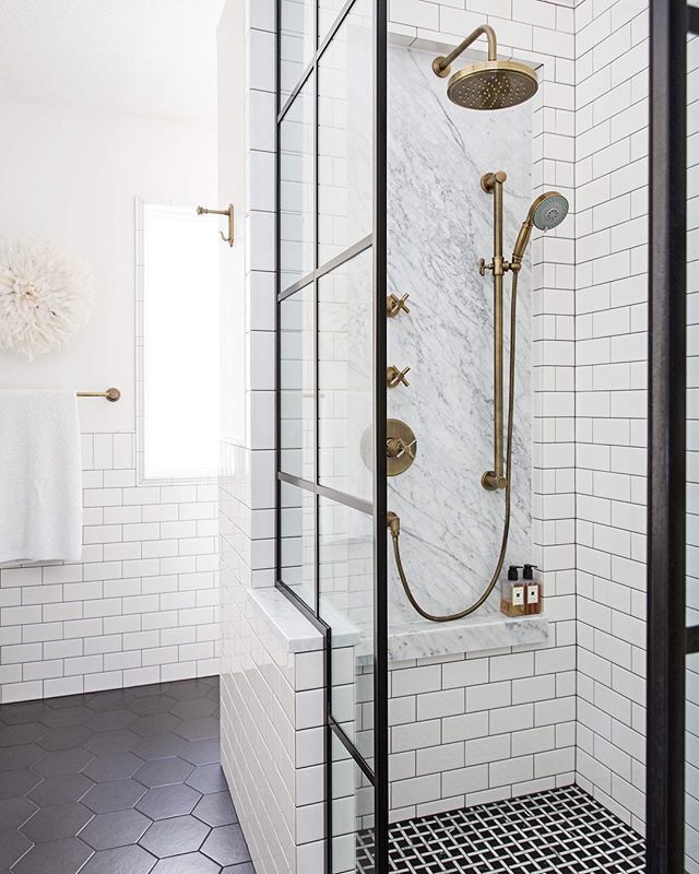 Monochromatic washroom with white tile and dark grout to highlight black shower door hardware