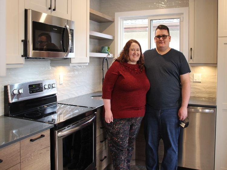 Couple Sharie and Corbin Spiderwick stand in their newly renovated kitchen