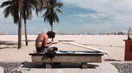Ein Surfer repariert sein Board am Strand von Rio de Janeiro