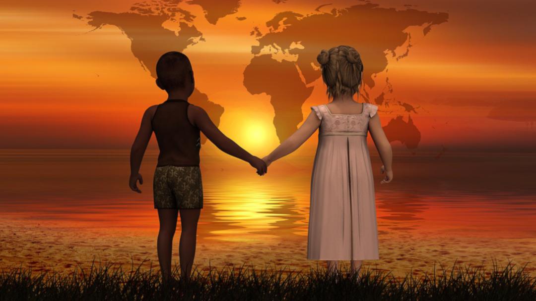 To barn hånd i hånd mot solnedgangen