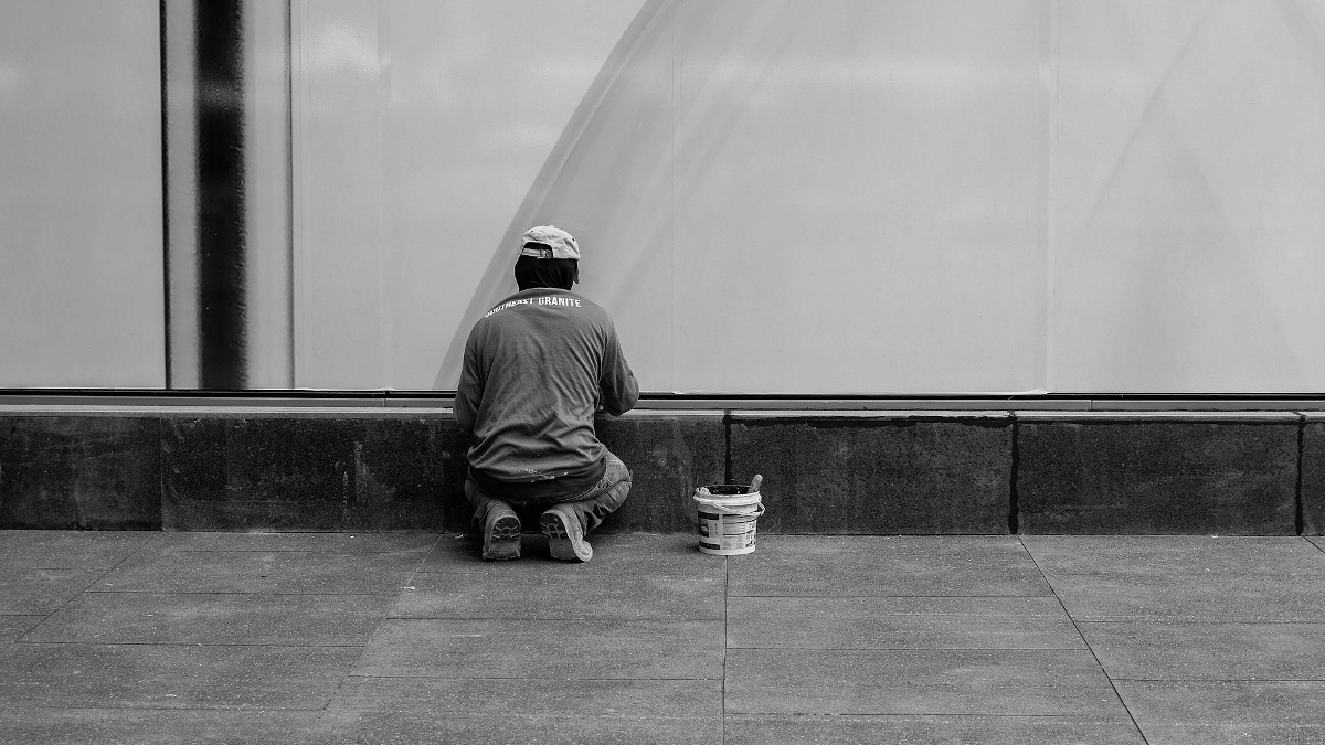 Mann på huk maler vegg
