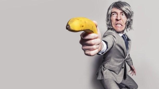 Mann i dress sikter på deg med en banan