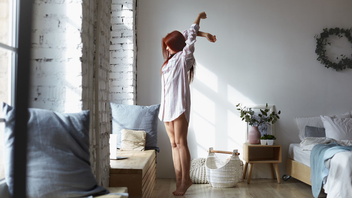 Full lenght shot of attractive young redhead female in long striped shirt standing barefooted on her toes in bedroom and stretching body, raising arms, facing big window, enjoying warm spring sunlight