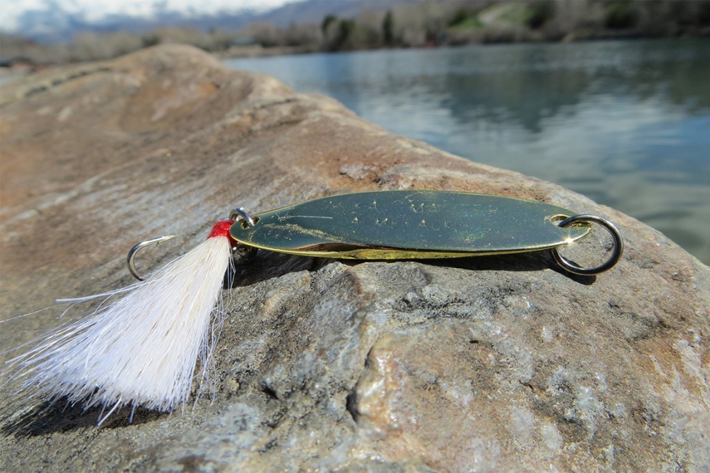 gold kastmaters fishing lure sitting on a rock by a river
