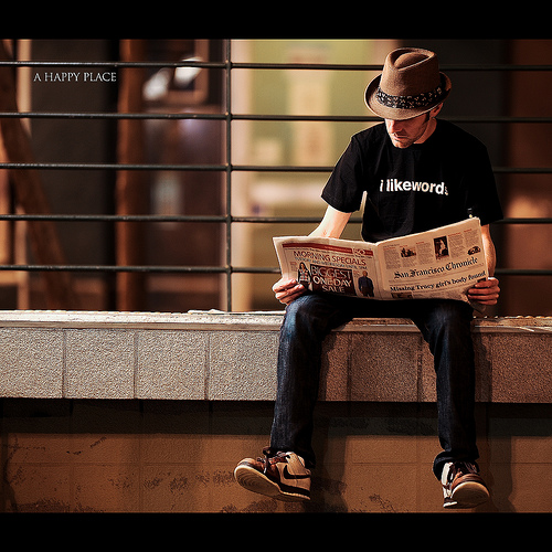 "hipster man in trilby hat with t-shirt that says ""i like words"" reading a newspaper while sitting on a loading dock."