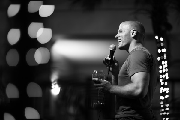 Tim Ferriss speaking at an event, smiling and holding a glass of wine.
