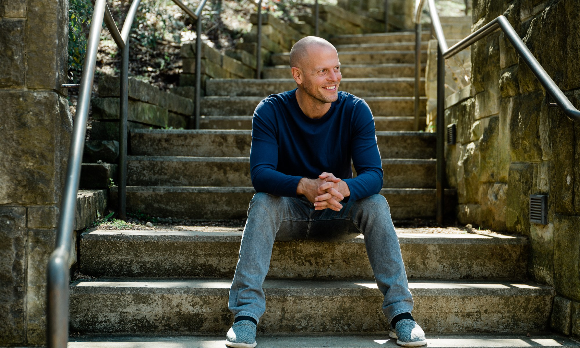 Tim Ferriss sitting outdoors on some stone steps and smiling.