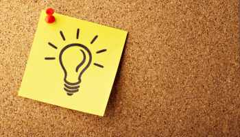 Post-it note with a light bulb drawing on a corkboard