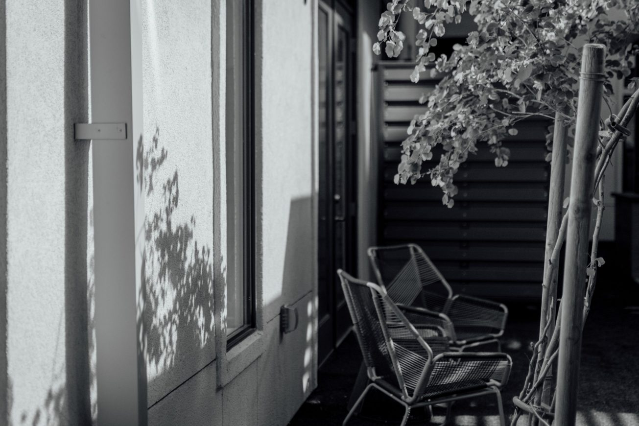 Black and white photo of some outdoor chairs in shadow.