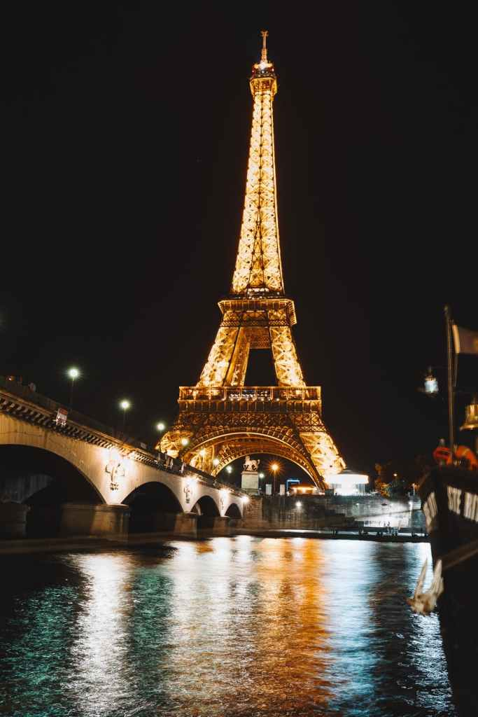 low angle shot of the eiffel tower with illuminated light at night