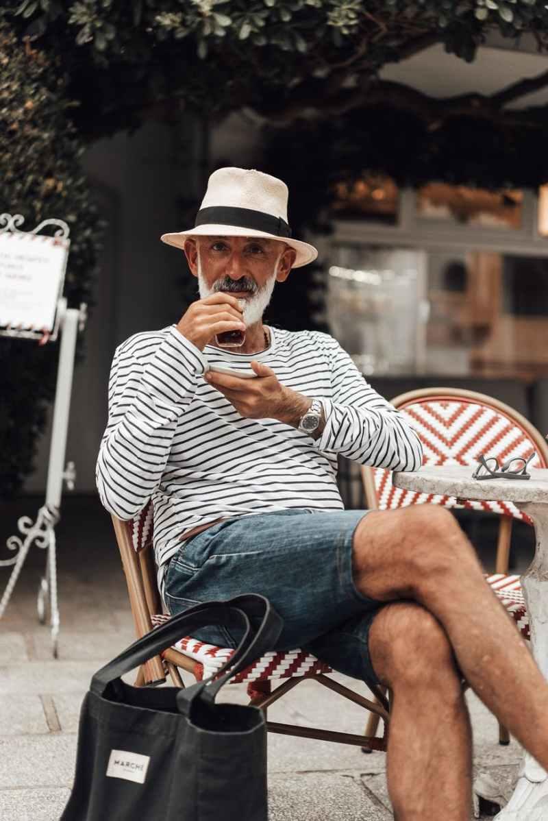 content senior ethnic man enjoying coffee in outdoor cafe