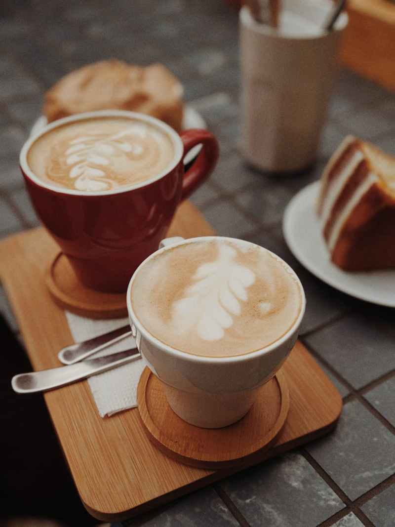 two cups of brown coffee on top of brown tray