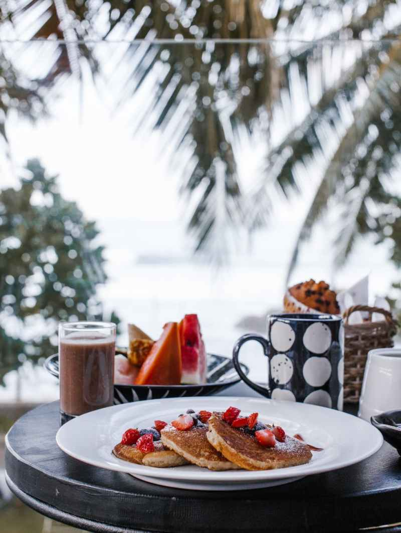 delicious pancakes and fruits placed near cold coffee during breakfast on terrace