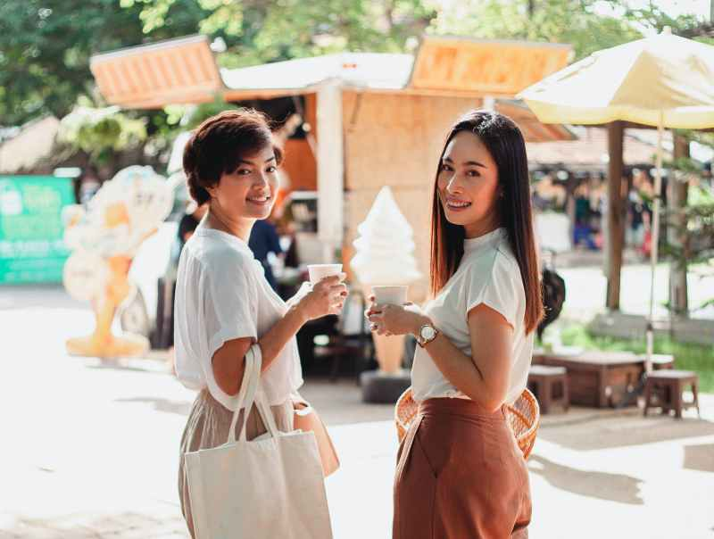 content asian women standing with cups of coffee in market