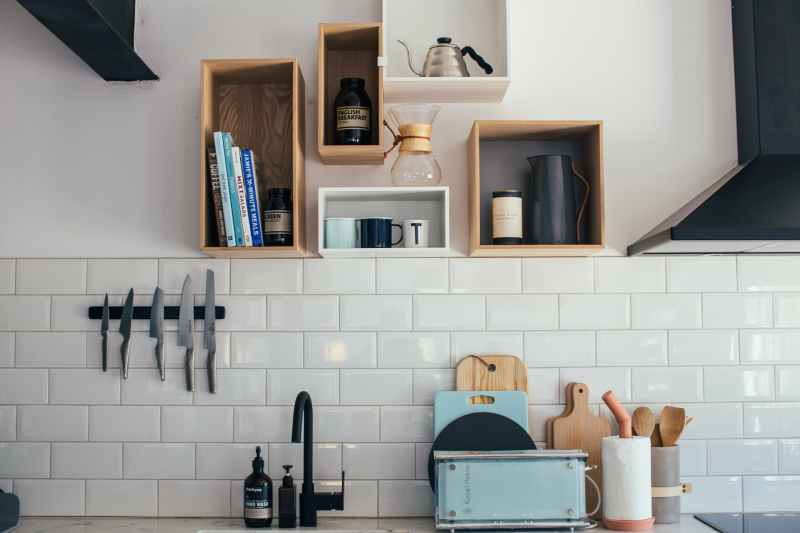 light kitchen with wooden shelves with various utensils and tiled wall