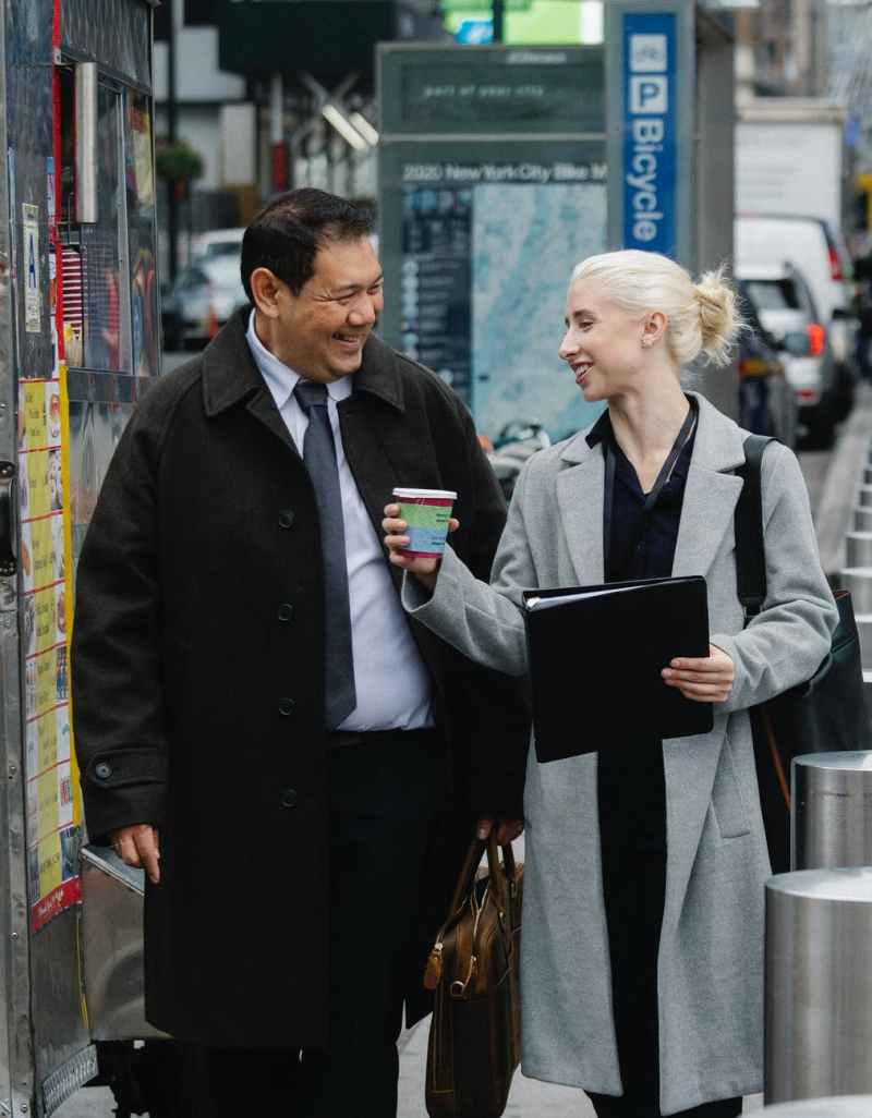multiethnic coworkers having coffee break on street