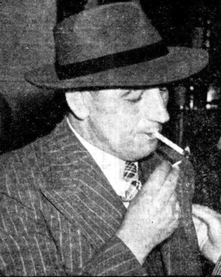 Mr H.W. Dedman lights up a cigarette in a Sydney pub after his big win on the horses.