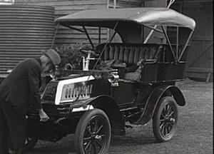 man cranking vintage car