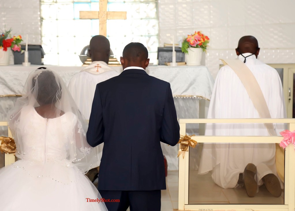 couple kneeling before the priest