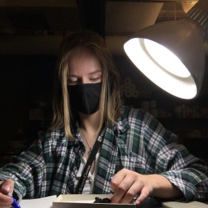 Charlotte Hohman in the lab making a list of important features on a dromaeosaurid upper jaw (maxilla) bone for her research