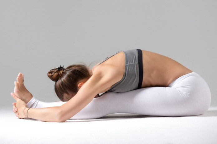 Seated forward bend yoga pose to start a 30-minute morning yoga sequence. Best and easy to do yoga poses for beginners to start an active day.