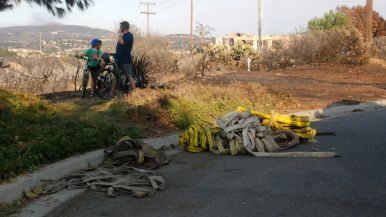 Neighbors view destruction as firefighters put out hot spots on Black Rail Road in Carlsbad.