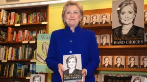 """Hillary Clinton holds her book, """"Hard Choices,"""" as she enters the bookstore."""