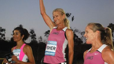 Tania Fischer waves to crowd after masters women's race.