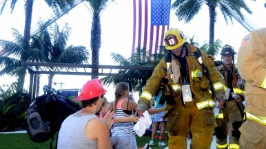 Spectators greet firefighters as they walk toward the Hilton staircase.