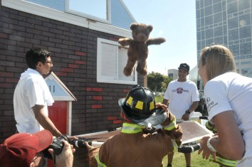 """Young children were invited to wear firefighter jackets and """"rescue"""" a teddy bear from a house."""