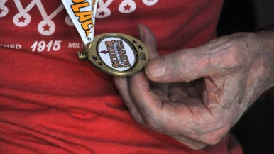 Pellmann examines his first of five gold medals at the San Diego Senior Olympics. Photo by Chris Stone