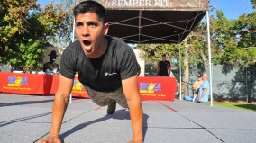 A Marine demonstrates perfect push-up technique for runners before the race. Photo by Chris Stone