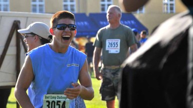 A runner laughs as his brother gets his hair cut. His turn was next. Photo by Chris Stone