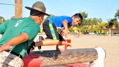 A boy jumps over a log as Drill Instructor Maldonado tells him to move faster. Photo by Chris Stone