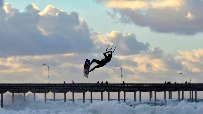 High winds fuel an impromptu kite-surfing performance for beach-goers at Ocean Beach.