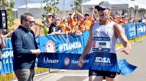 John Nunn reacts as he wins the men's Olympic Trials 50K race walk, defending his 2012 Trials victory. USATF Director of Events Jim Estes holds the tape. Photo by Ken Stone