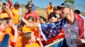 John Nunn reaches out to kids in Team Nunn T-shirts after winning men's Olympic Trials 50K race walk. Photo by Ken Stone