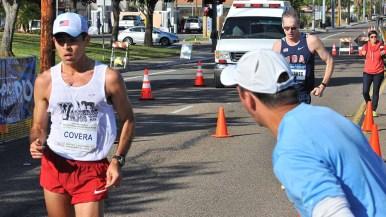 Two-time Olympian Tim Seaman yells encouragement to eventual 20K invitational winner Emanuel Corvera. Photo by Ken Stone