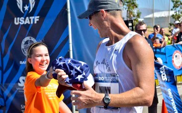 Ella hands her dad John Nunn the American flag a second after he won his third trip to an Olympic Games. Photo by Ken Stone