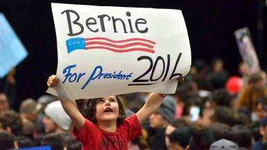 A young boy holds a handmade sign at Sanders rally. Photo by Chris Stone