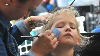 A young girls gets a mouse facing painting applied at the science and engineering festival. Photo by Chris Stone