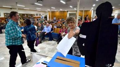 An attendee deposits a ballot next to a cardboard Bernie Sanders. Photo by Chris Stone