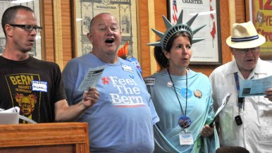 Potential delegate Jim Boydston, a former San Diego Opera tenor (second from left), leads attendees in a Bernie Sanders anthem. Photo by Chris Stone