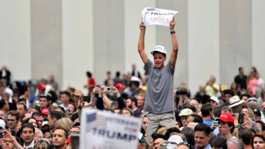 A young Trump fan stands above the crowd before the speech. Photo by Chris Stone