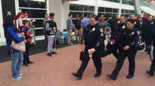 Police are cheered and applauded as they arrive at 6:35 a.m. at San Diego Conventon Center. Photo by Ken Stone